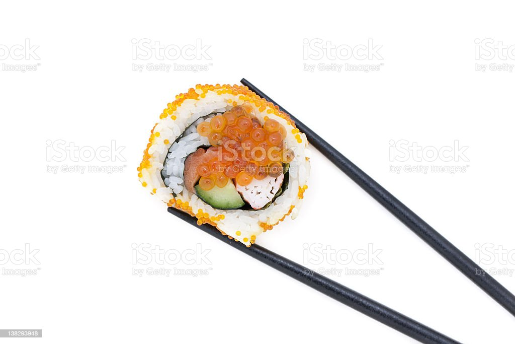 Chopsticks holding a single piece of sushi roll royalty-free stock photo