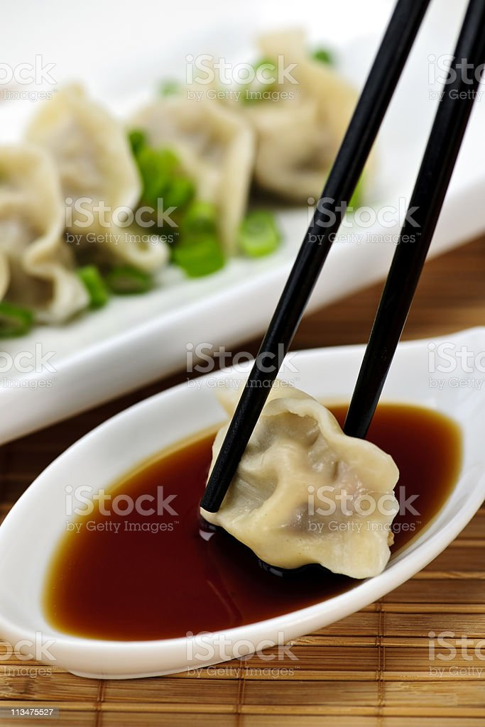 Chopsticks holding a steamed dumpling in a bowl of soy sauce stock photo