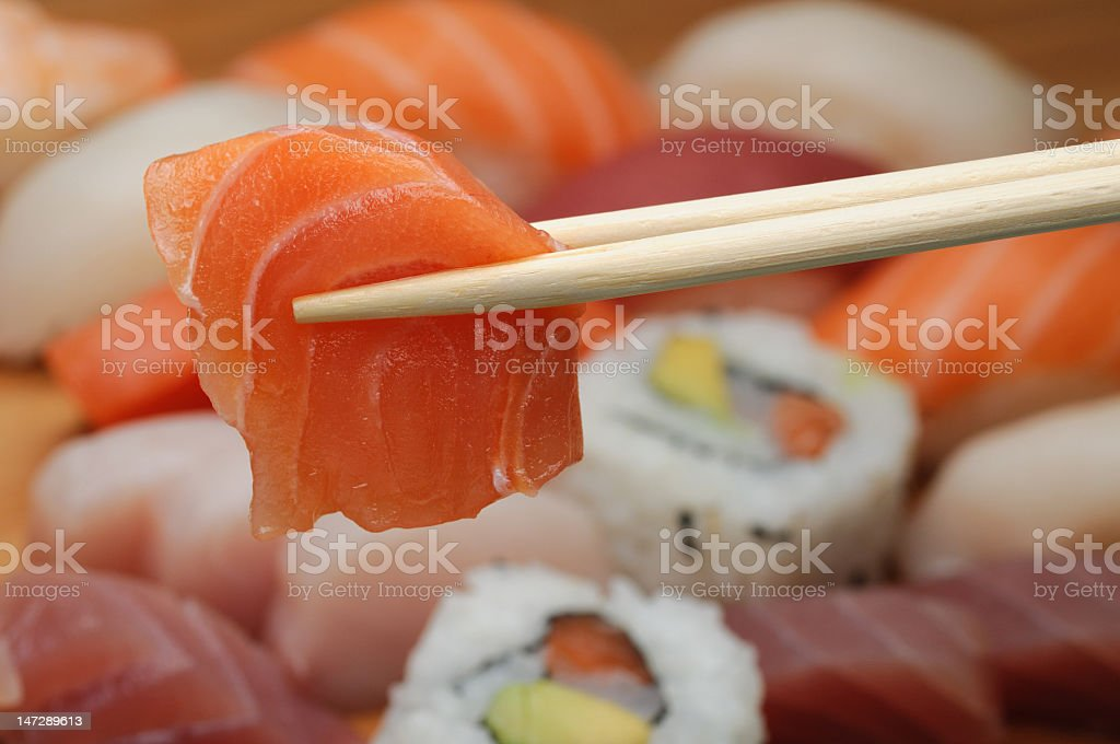 Chopsticks holding raw salmon above a sushi platter royalty-free stock photo