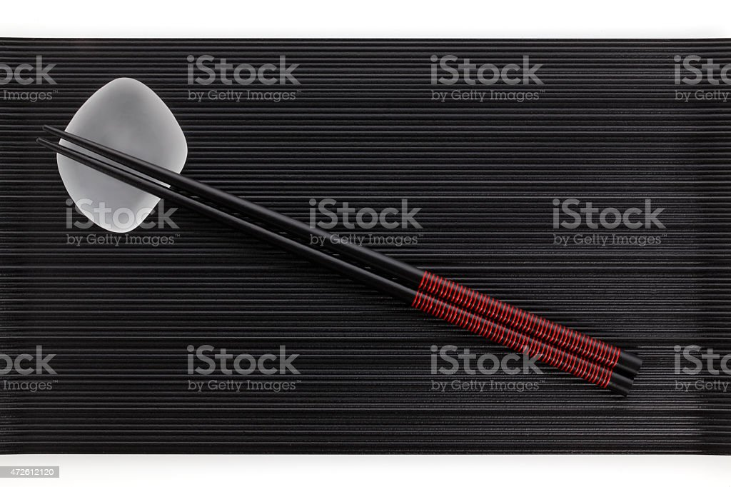 Chopsticks on black lacquering plate stock photo