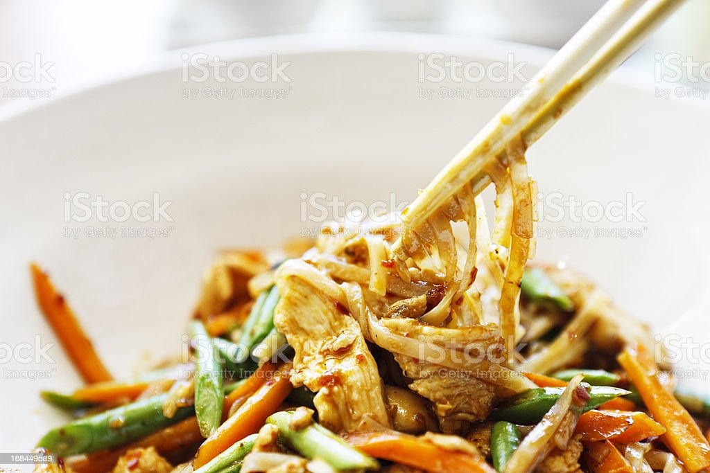 Chopsticks taking food from dish of stir fried Thai chicken royalty-free stock photo