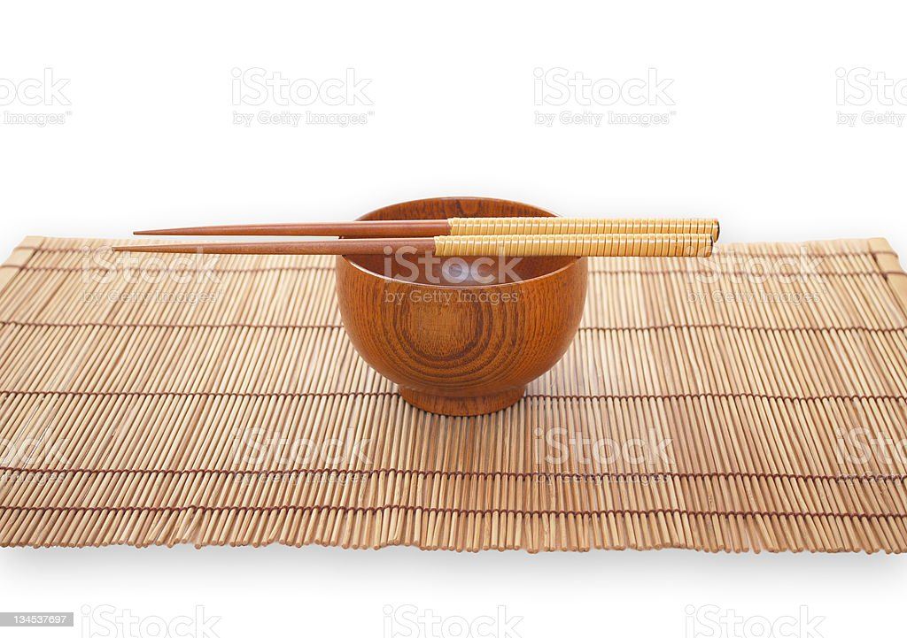 Chopsticks with wooden bowl on bamboo matting background royalty-free stock photo
