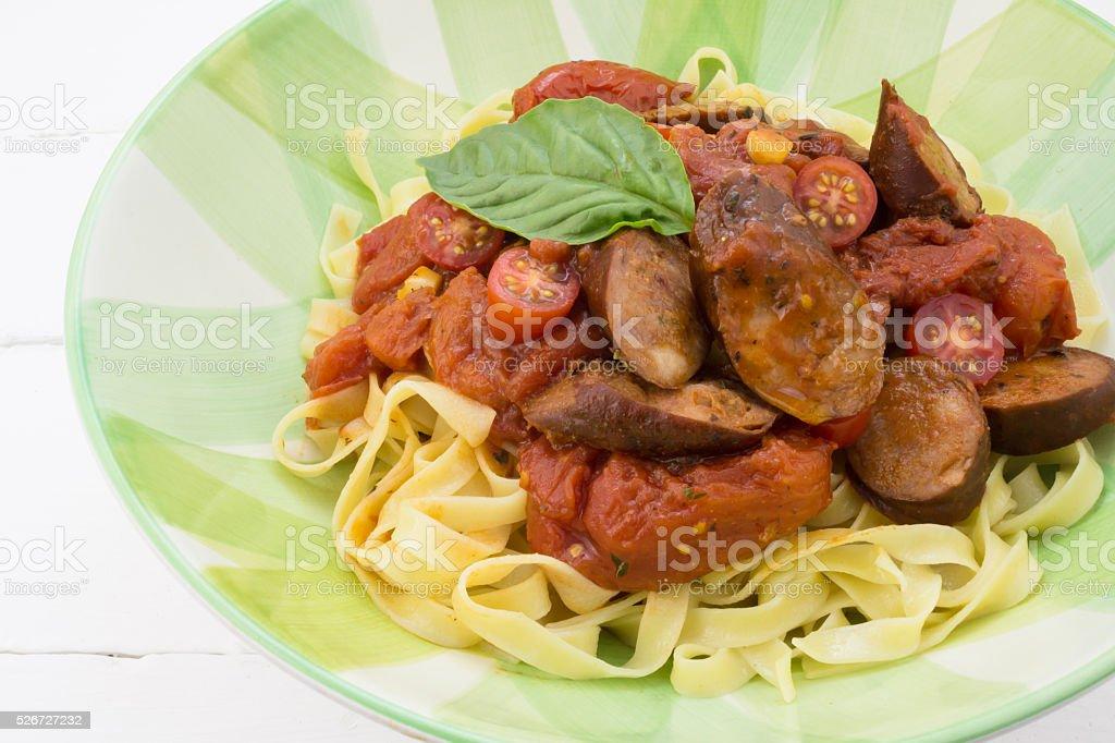 Chorizo sausage and tomato pasta meal with basil stock photo