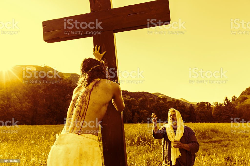 Christ Pushes Up His Cross as Apostle Looks On stock photo