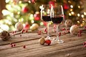 Christams Holiday Red Wine on Wood Table and Christmas Tree