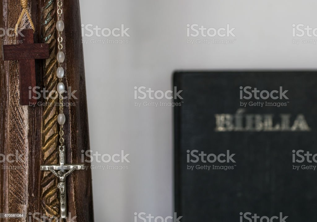 Christian and catholic Jesus Christ cross crucifix rosay made of wood and jewelery with a bible in the background - Religion, catholicism, belief, god concept and idea stock photo