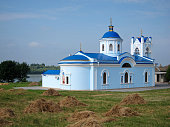 Christian church with blue roof near heap of dry grass