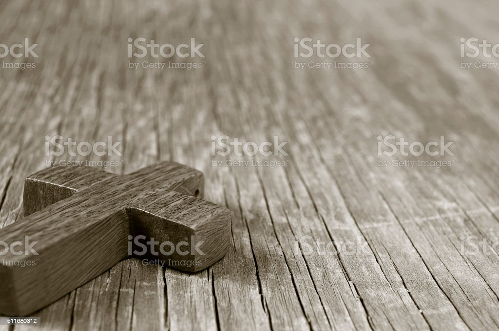 Christian cross on a rustic wooden surface, sepia toning stock photo