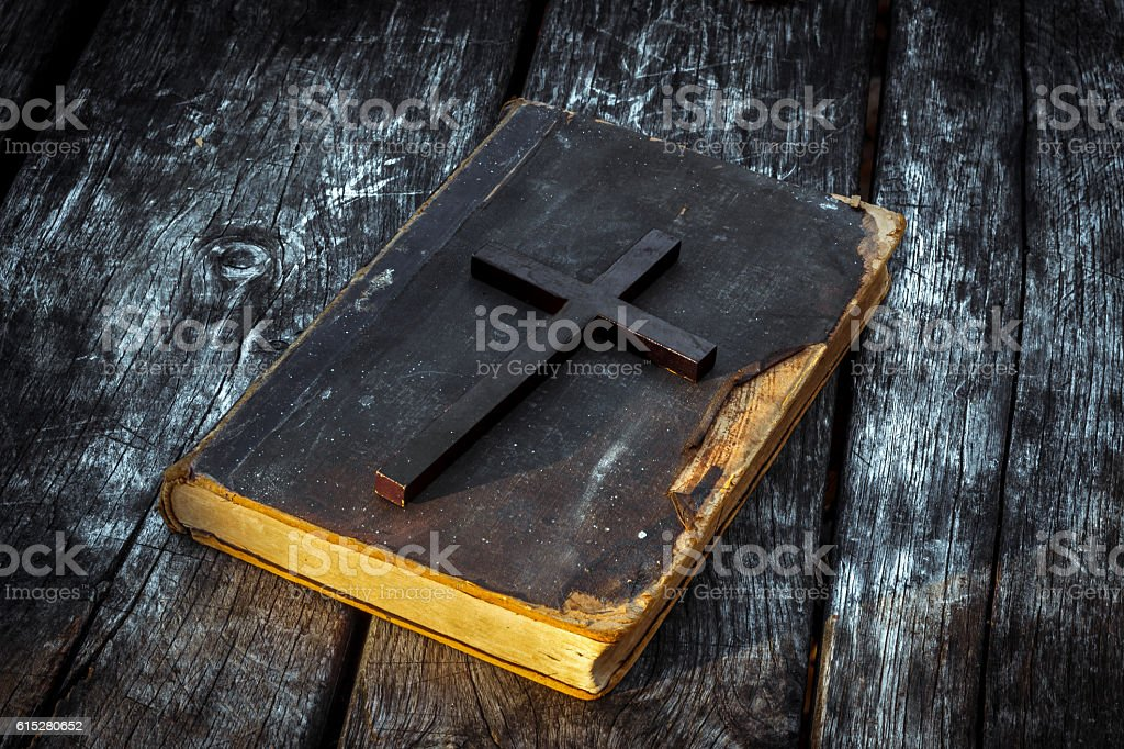 Christian cross on bible, burning candle and prayer beads stock photo