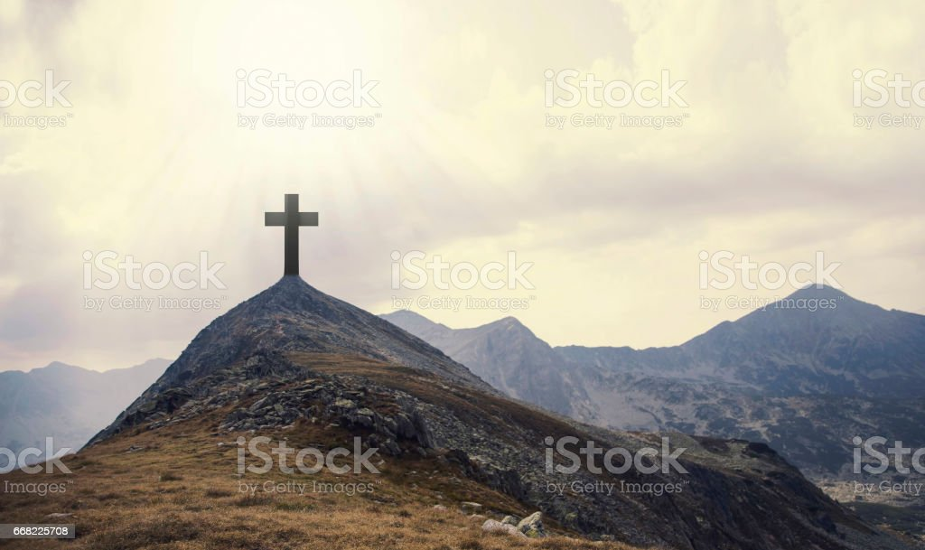 Christian cross on top of the hill with sunrays, crucifixion, religious concept stock photo