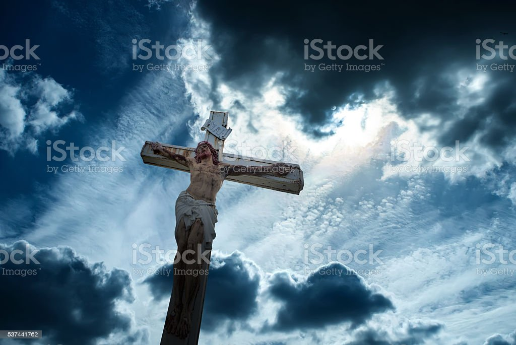 Christian cross over dark stormy sky background stock photo