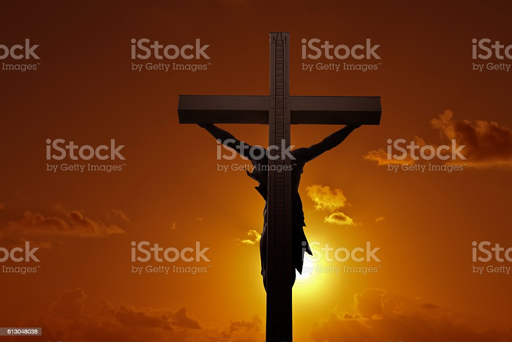 Christian cross with Jesus Christ over sunset stock photo