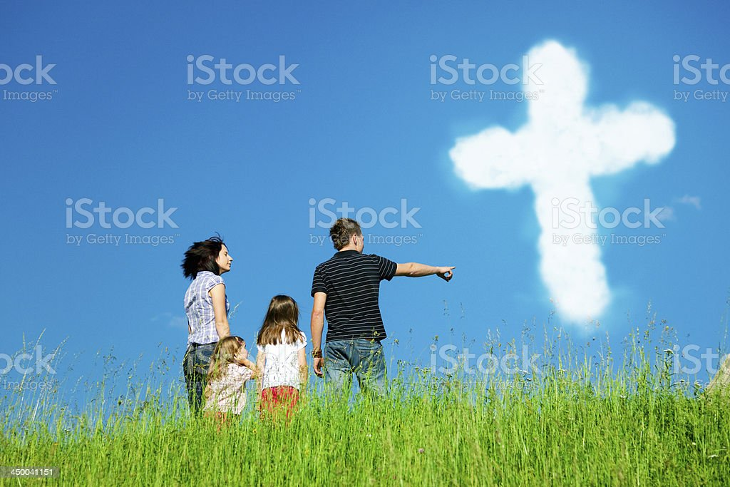 christian family looking at clouds forming the holy cross stock photo