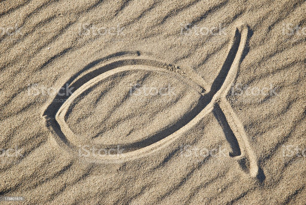 Christian Jesus Fish Symbol in the Sand stock photo
