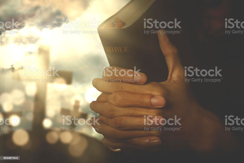 Christian person praying with bible stock photo
