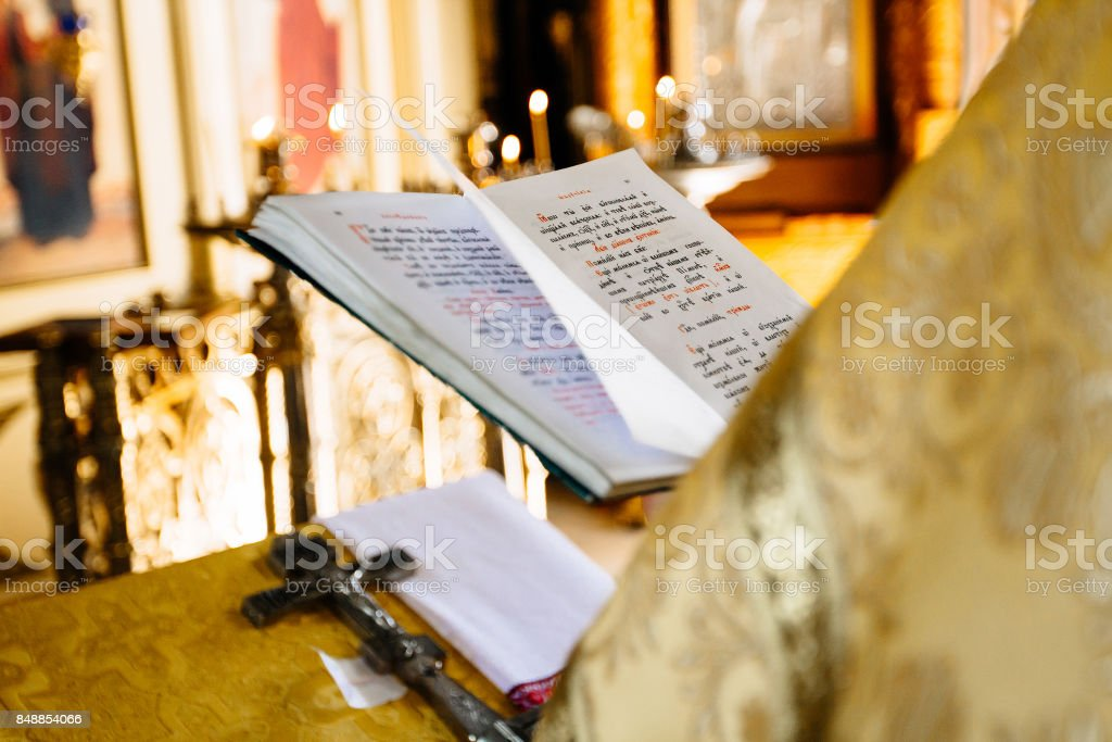 christian priest reading church book, priest reads a pray over the Bible stock photo