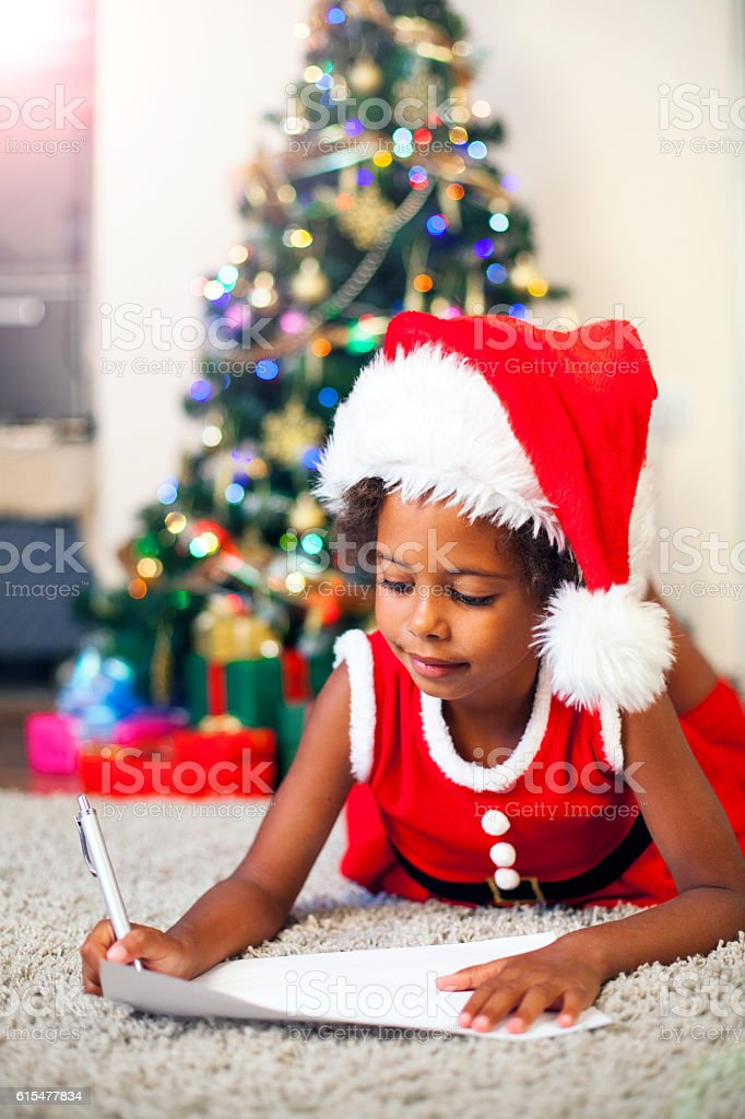 Christmas African American Child Writing a Letter to Santa Claus stock photo
