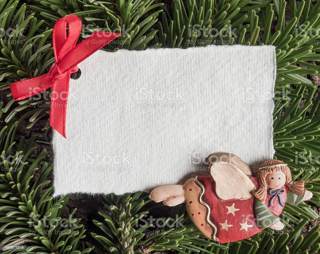 Christmas, angel, blank paper on evergreens stock photo