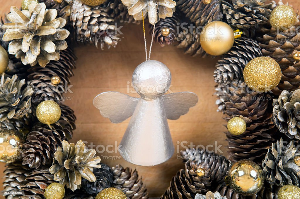 Christmas angel with wreath of cones on background stock photo