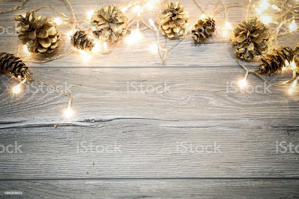 Christmas background with cones on wooden table with copy space.