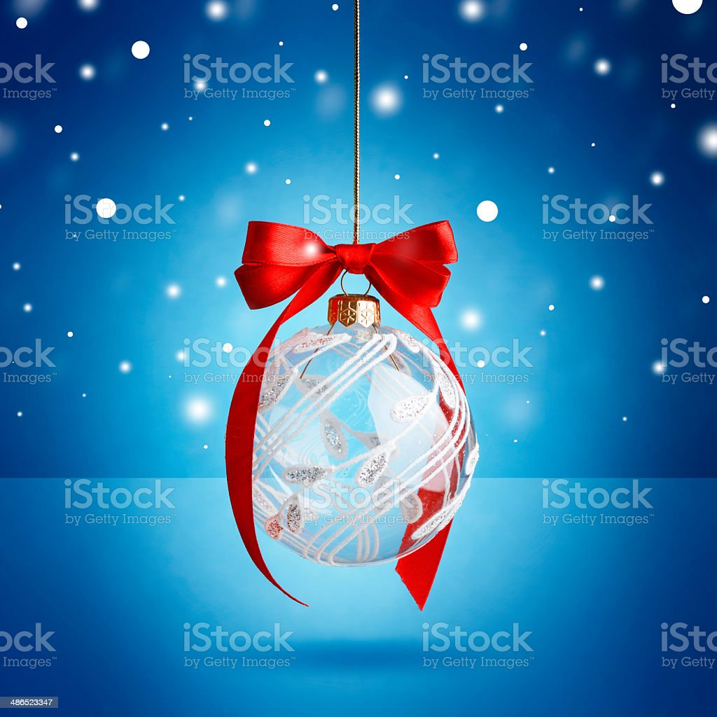 Christmas ball hanging with ribbon on blue background stock photo