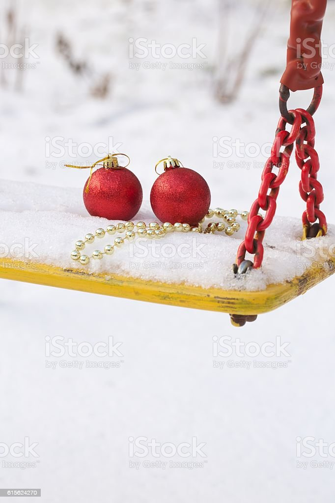 Christmas balls in the snow on a swing seat stock photo
