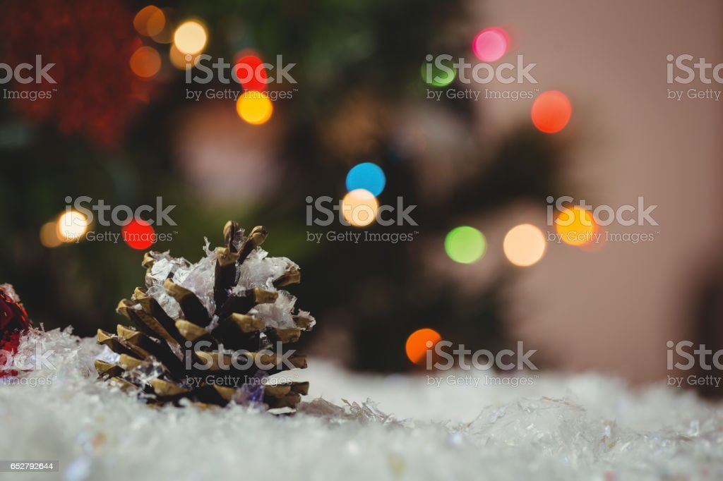 Christmas bauble and pine cone on snow stock photo