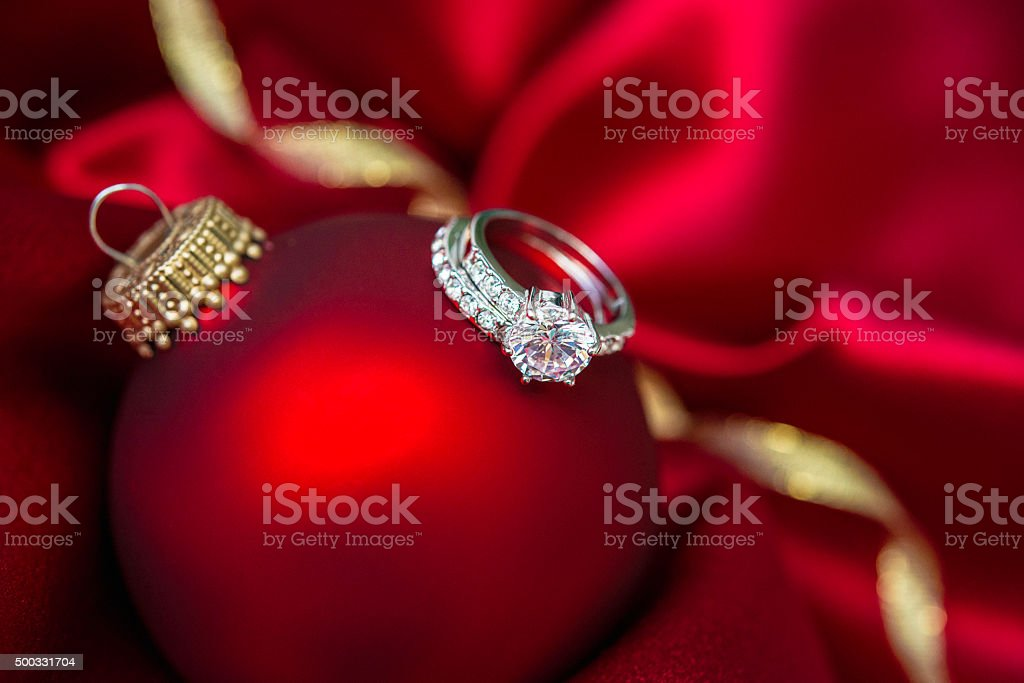 Christmas bauble with wedding and engagement rings in red satin stock photo