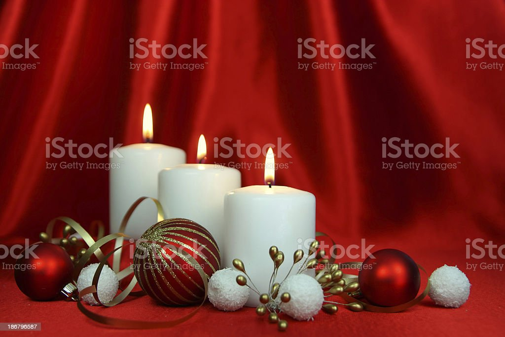 Christmas baubles and candles on a red silk backdrop royalty-free stock photo