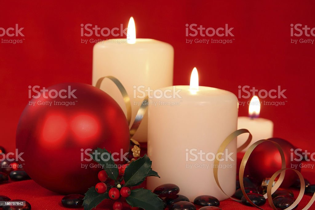 Christmas baubles and white candles on a red silk backdrop royalty-free stock photo