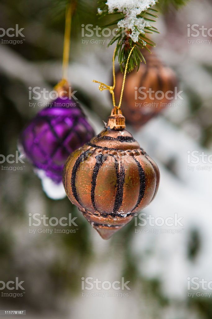 Christmas baubles on a snowy pine stock photo