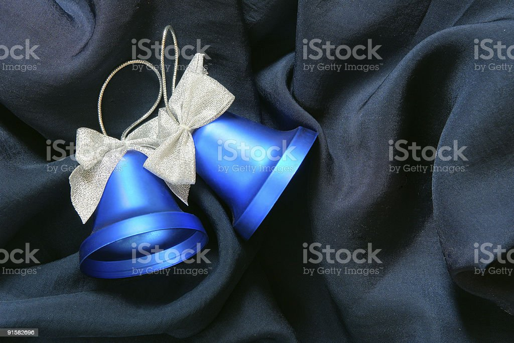 Christmas bells over fabric background royalty-free stock photo