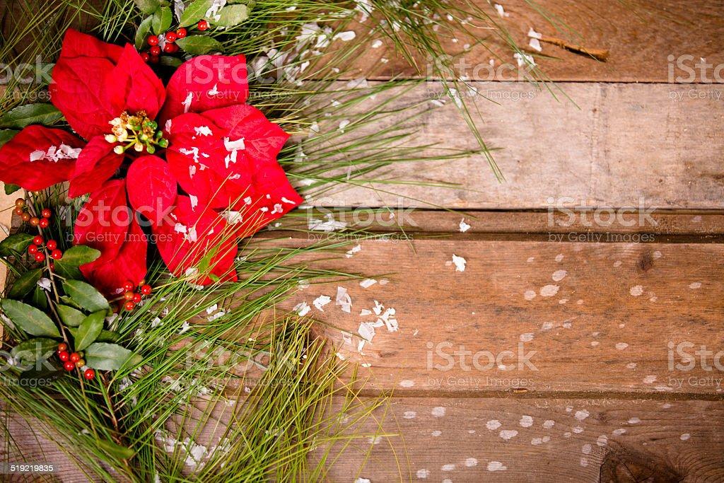 Christmas border. Poinsettia, pine tree branch, holly, snow. Wooden table. stock photo
