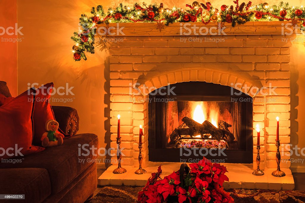 Christmas brick arched fireplace with fire, Poinsettias,candles (P) stock photo
