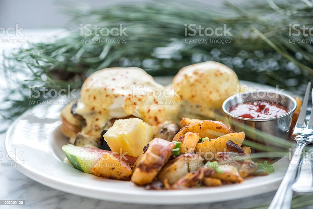 Christmas Brunch of Eggs Benedict, Mushrooms, Hash Brown Potatoes, Fruit stock photo