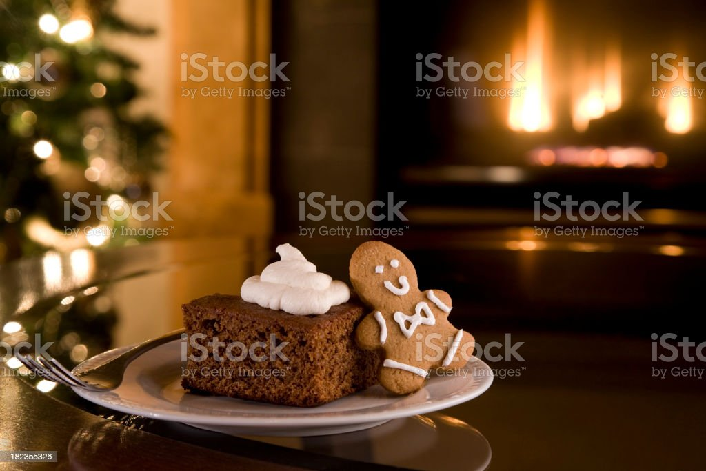Christmas cake and cookie on a table in front of fireplace royalty-free stock photo
