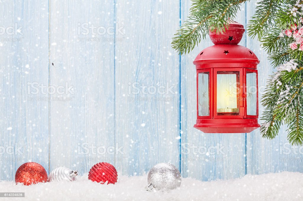 Christmas candle lantern on fir tree branch in snow stock photo