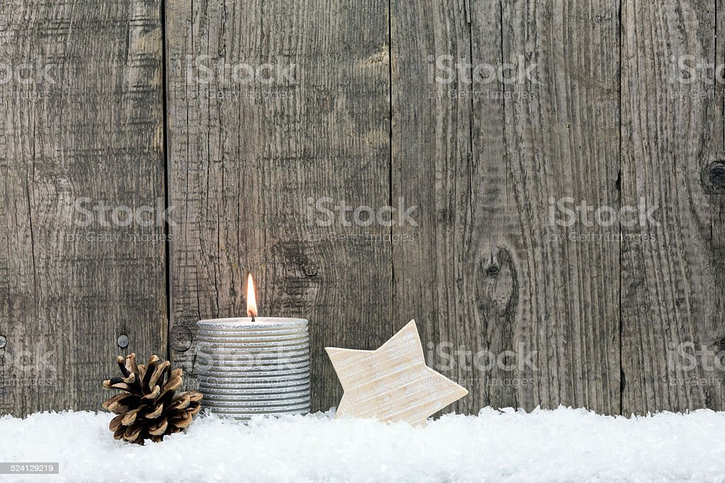 Christmas candle, wooden star and pin cone stock photo