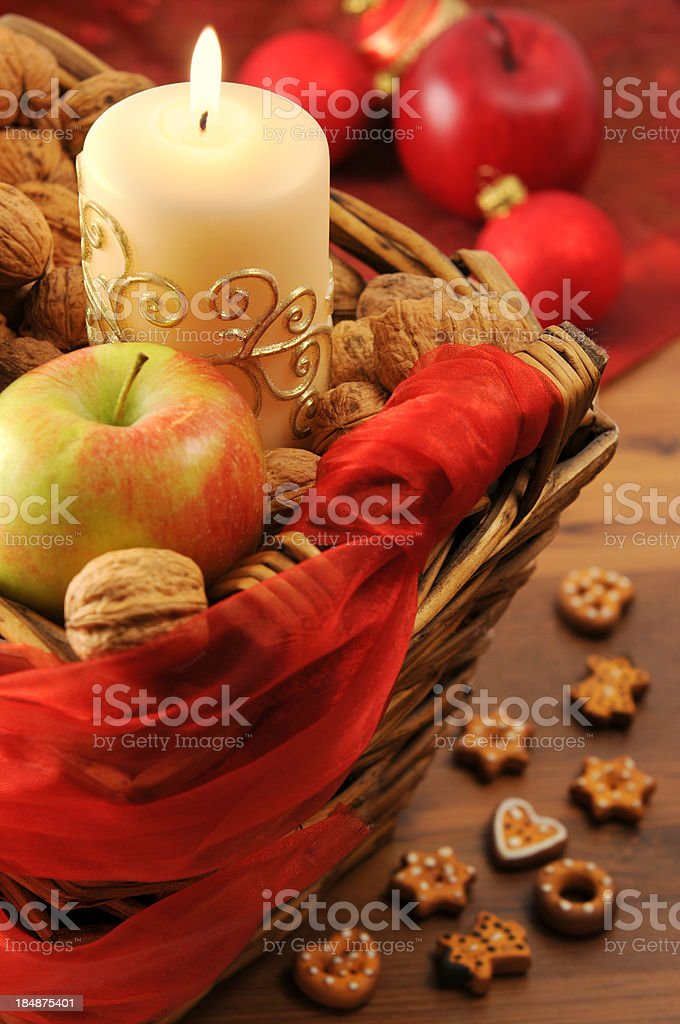 Christmas Candles and appel in Basket with cookies on table royalty-free stock photo