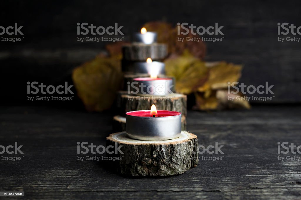 Christmas candles burning, decoration with wooden logs resting o stock photo
