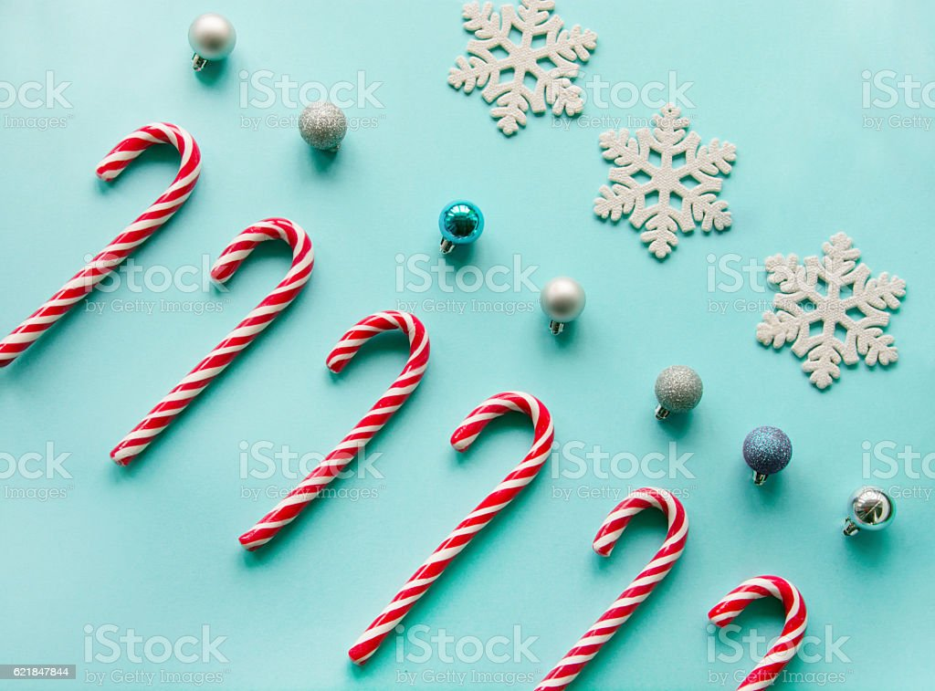 Christmas candy cane in row on blue background. Flat lay. stock photo