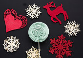 Christmas candy with decor on black. Top view and copyspace.