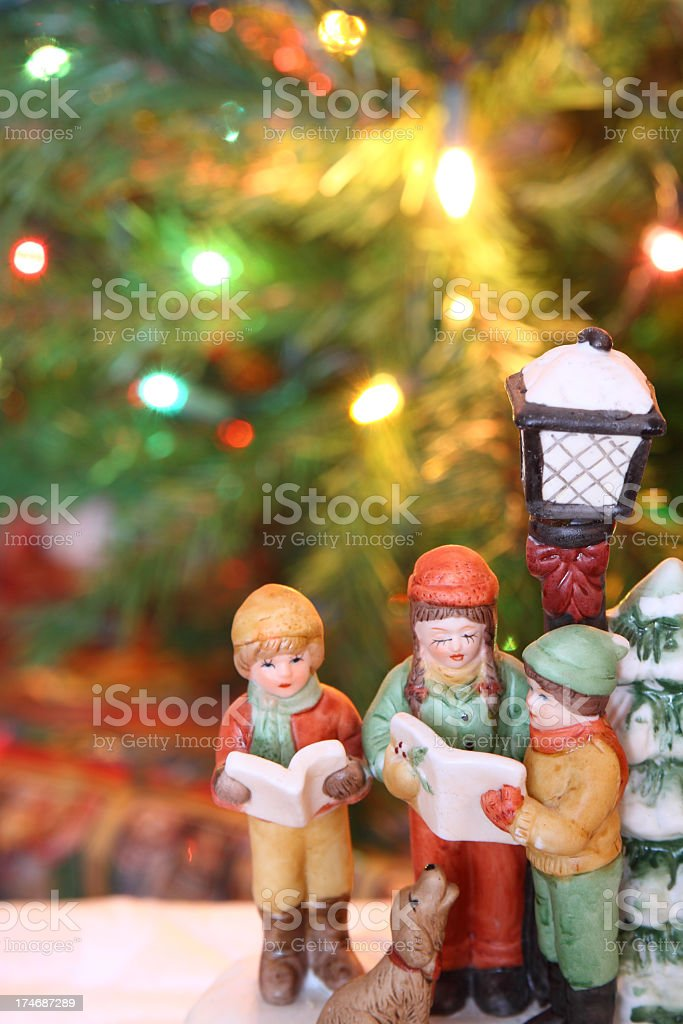Christmas carolers figurines over a Christmas background stock photo