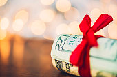 Christmas cash. Wad of American currency tied with red ribbon