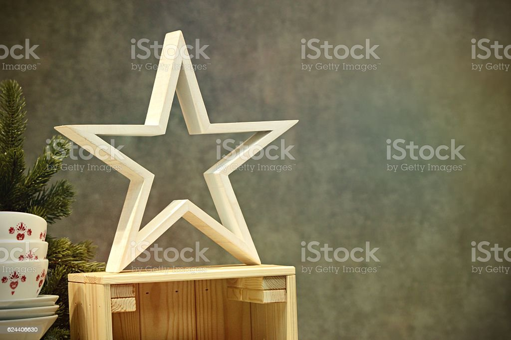 Christmas Celebration Theme Wooden Star with xmas tree in background stock photo
