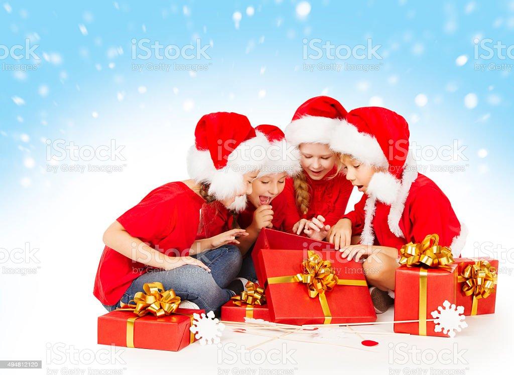 Christmas Children Open Presents, Kids Santa Hat, Group Girls Boys stock photo