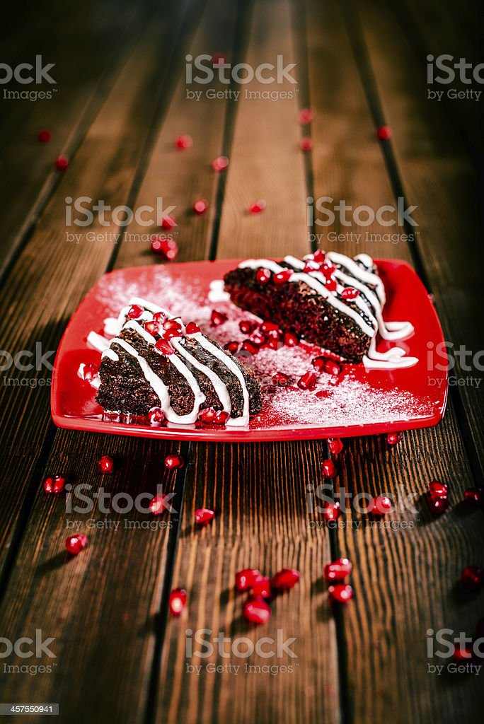 Christmas chocolate cake dessert with pomegranate on wooden table royalty-free stock photo