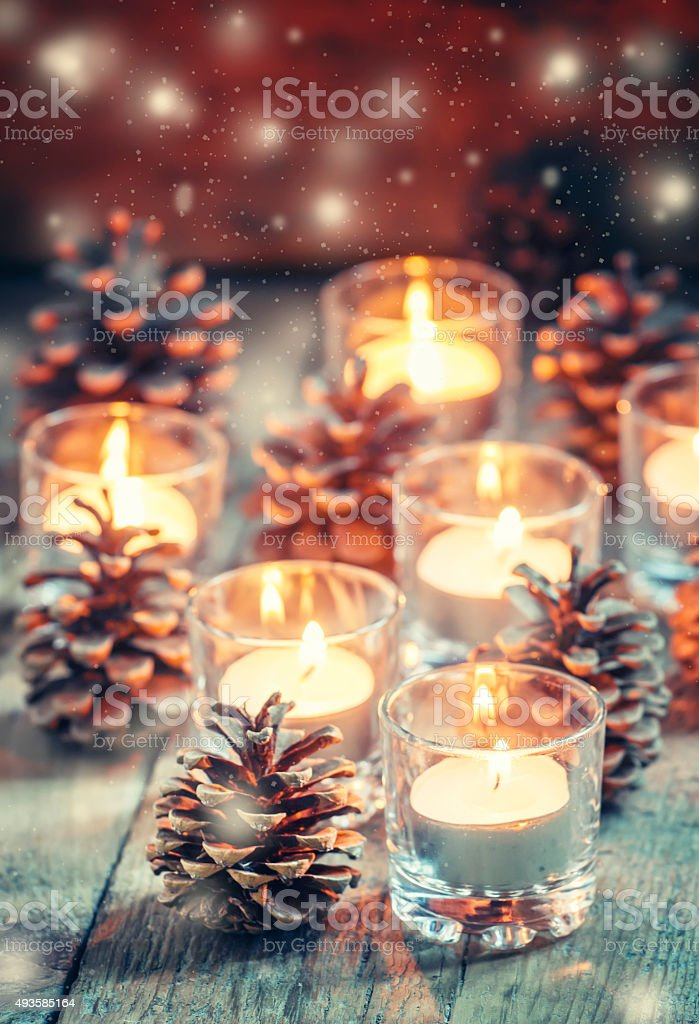 Christmas Christmas card with glowing small candle and fir cones stock photo