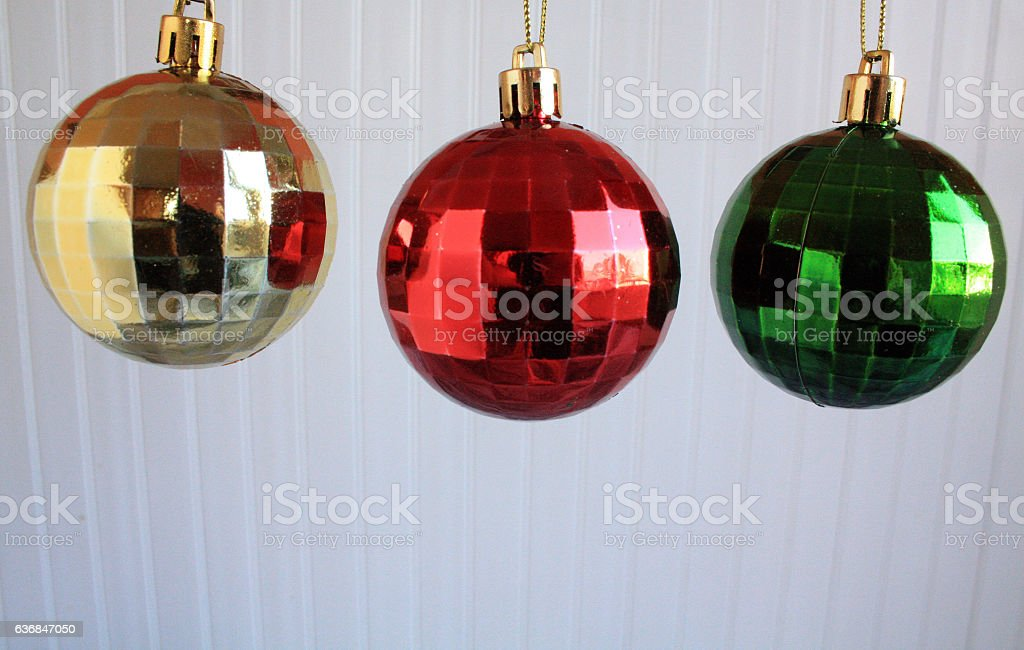 green red and gold Christmas balls hanging on a white wooden...