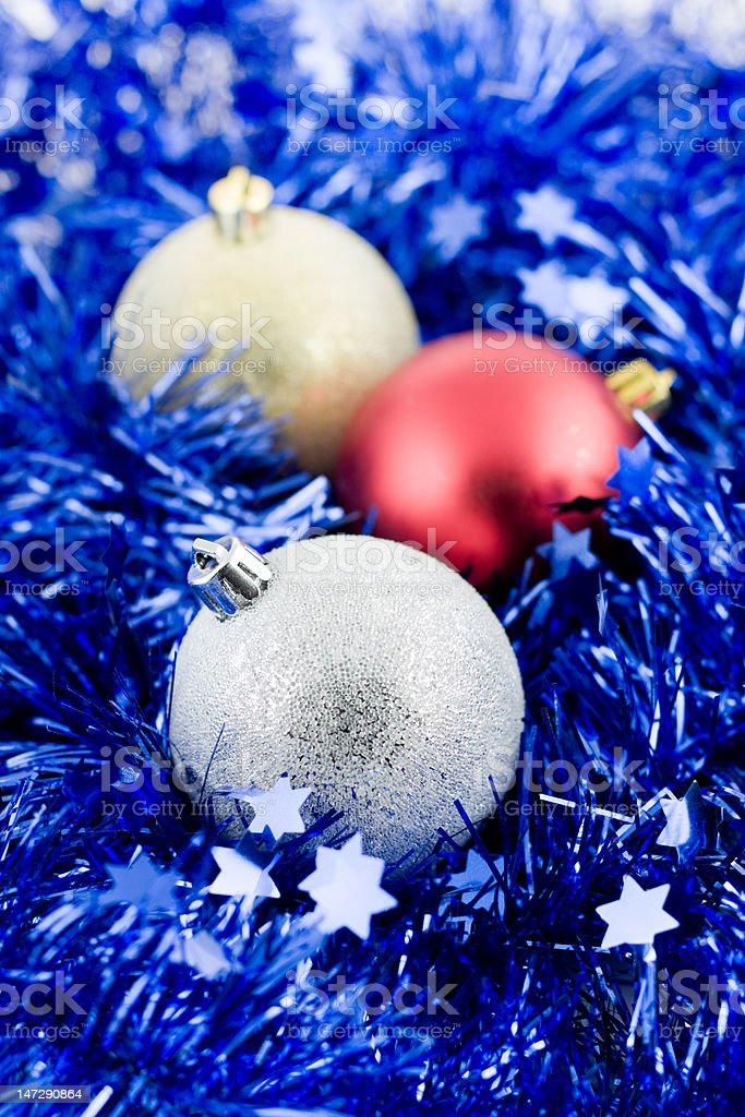 christmas colored balls in blue tinsel vertical orientation soft focus royalty-free stock photo